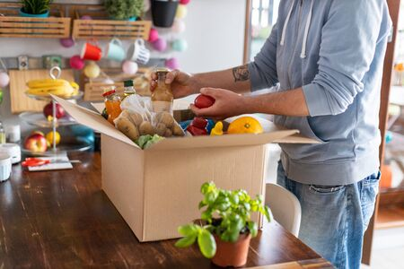 Young man unpacking boxes of food at home