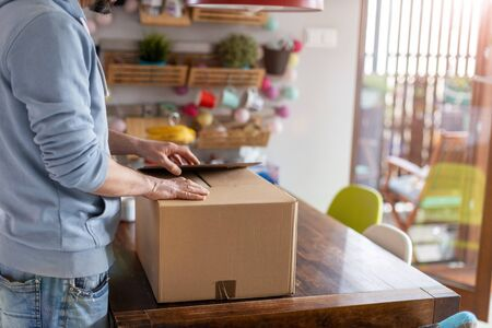 Young man unpacking parcel ordered online at home