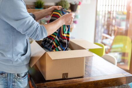 Man at home unpacking parcel with clothing