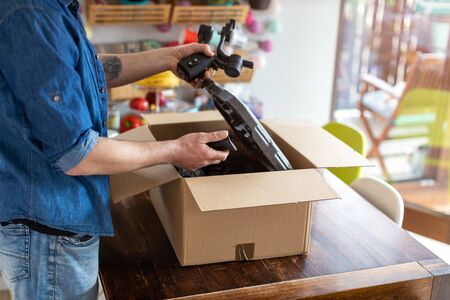 Man unpacking parcel with tools ordered online