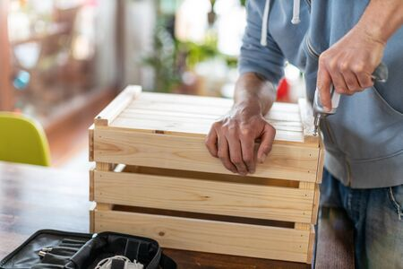 Man drilling wooden crate with power tool at home