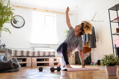 Young woman doing fitness exercise at home