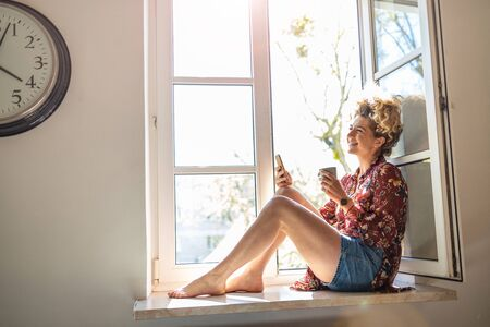 Young woman sitting on window sill and using smartphone