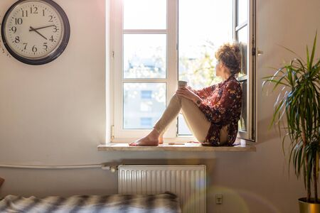 Young woman sitting on window sill