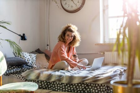 Young woman working in bed at home with laptop