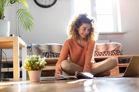 Female student learning in home setting with laptop and books Banco de Imagens