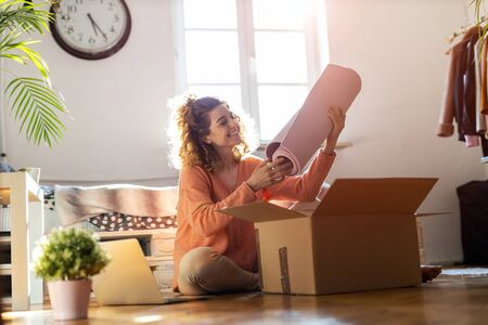 Woman unpacking box with workout equipment at home