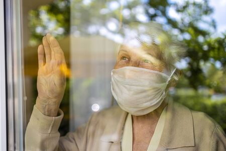 Senior woman looking out of window at home Stockfoto