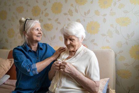 Woman helping senior woman dress in her bedroom Foto de archivo