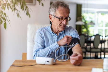 Senior man using medical device to measure blood pressure