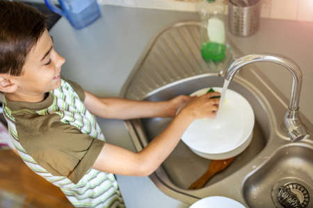 Little boy washing the dishes in the kitchen sink