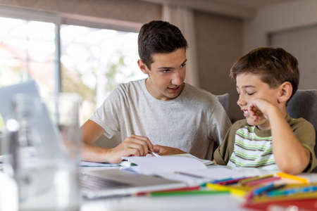 Teenage boy helping his younger brother doing homework at home Archivio Fotografico