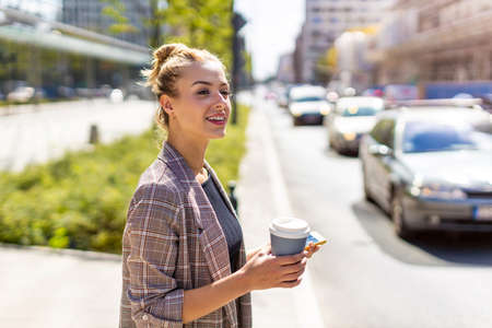 Young Woman Moving Through A City Holding Coffee Stockfoto