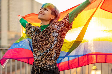 Portrait of happy non-binary person waving rainbow flag