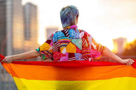 Back view of a person holding rainbow flag on city street