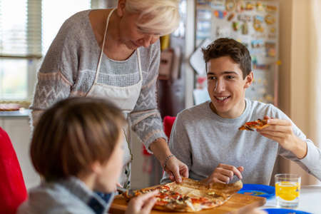 Mother and sons eating pizza for lunch at home