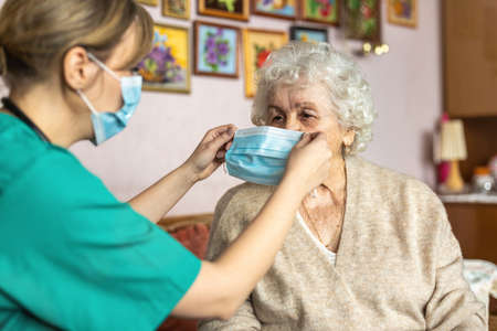 Female nurse helping a senior woman to put on protective face mask during home visit