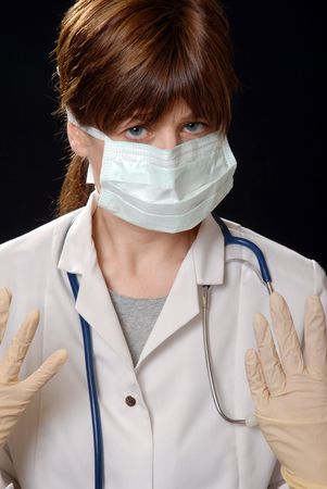 cute young lady doctor, masked with latex gloves, on black Stock Photo