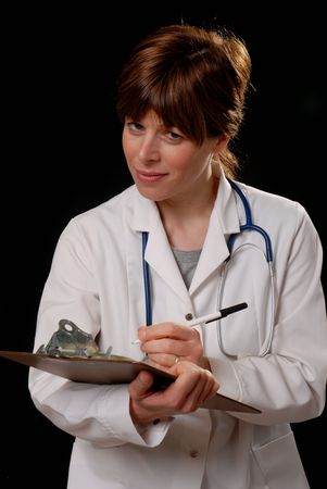prescribing: attractive young lady doctor in white coat with stethosope making notes - on black background