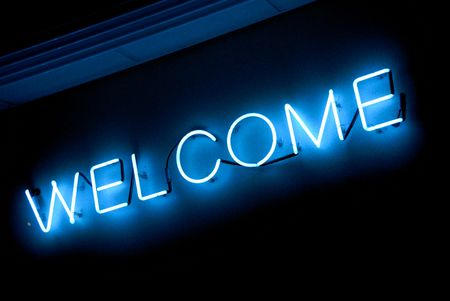 illuminated blue neon welcome sign at night photo