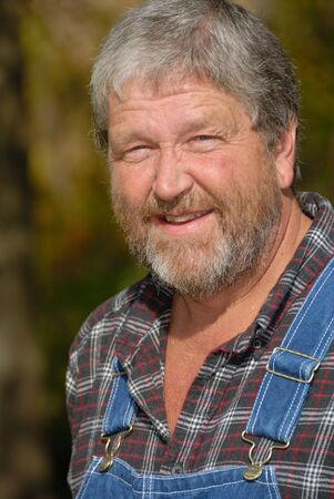 grey haired: portrait of grey haired bearded farmer, wearing bib overalls & plaid shirt in meadow Stock Photo