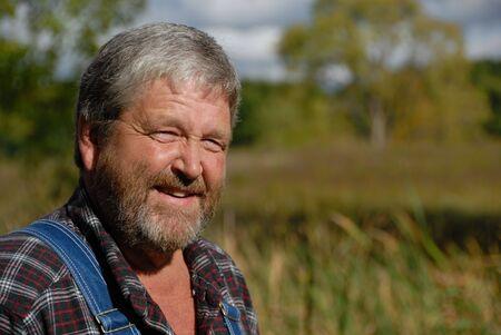 chemise carreaux: Portrait de paysan barbu aux cheveux gris, v�tu d'une salopette et bib plaid shirt en prairie Banque d'images