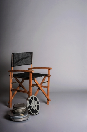 Directors cut concept of movie director chair with 16mm film spools photo