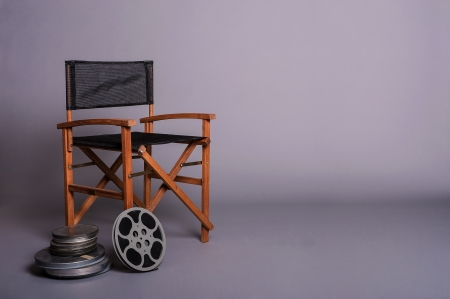 Directors cut concept of movie director chair with 16mm film spools
