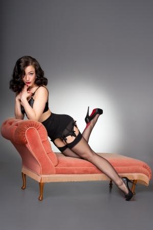 klassieke pinup in zwarte lingerie op vintage chaise
