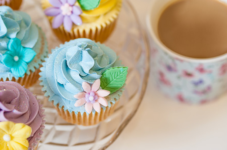 Cupcake selection in pastel colors with cup of tea photo