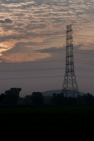 High voltage power transmission towers in sunset sky background Фото со стока