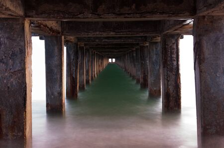 Tunnel effect with emerald colored water at the beach in the evening