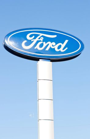 The logo of Ford on the road sign against blue sky in vertical format