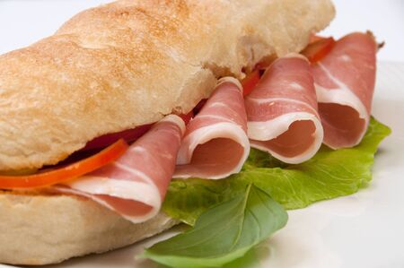 sandwich with tomato and ham on white dish photo