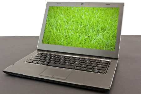 laptop with green grass on black background photo