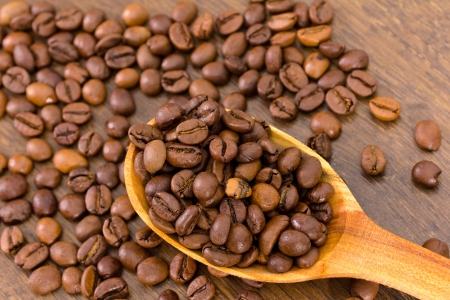 Wooden spoon with coffee beans on wooden background Stock Photo - 16449243