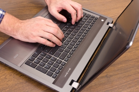 a man presses the buttons on laptop photo