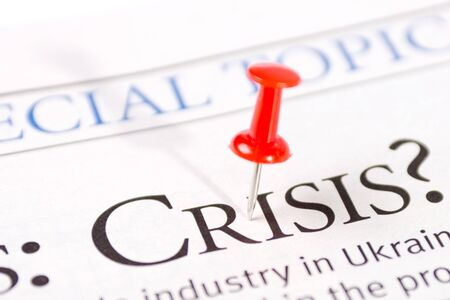 political and social issues: word a crisis is written in a newspaper