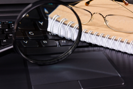 glasses and notebook lie on the keyboard of computer Stock Photo - 17965068
