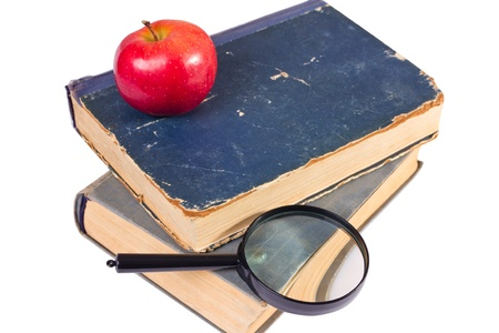 few age-old books, apple and magnifying glass photo