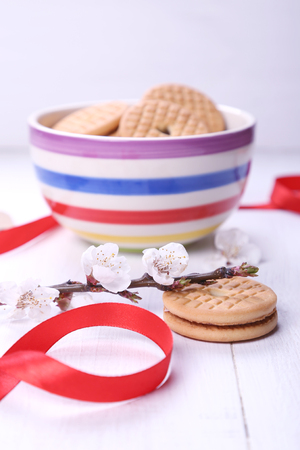 few cookie in a bowl and by flowers on a branch