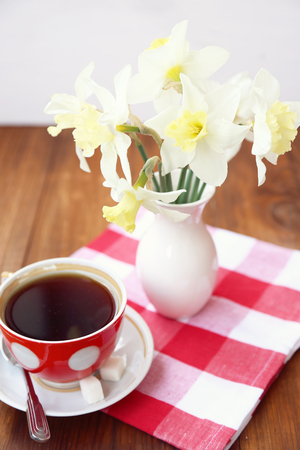 few narcissuses are in a vase, alongside cup with tea