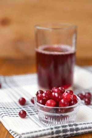 ripe wet cranberries and juice on wooden background photo