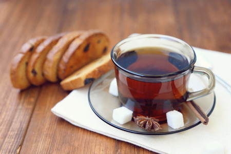 fresh tea in transparent cup,with rusks on wooden background photo