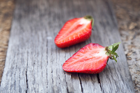 bisected: ripe strawberry is bisected, on a wooden background