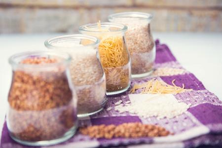 capacities: buckwheat, rice, macaronis and wheat groats, is in glass capacities, in a studio Stock Photo