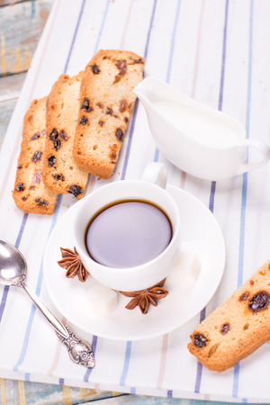 anis: fresh coffee with anis,cake and milk on wooden background