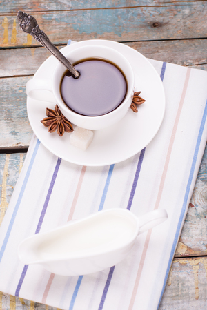anis: fresh coffee with anis,sugar and milk on wooden background