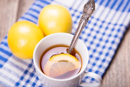 yellow tea pot: tea with ripe fresh lemon,cookies,sugar,cinnamon in studio