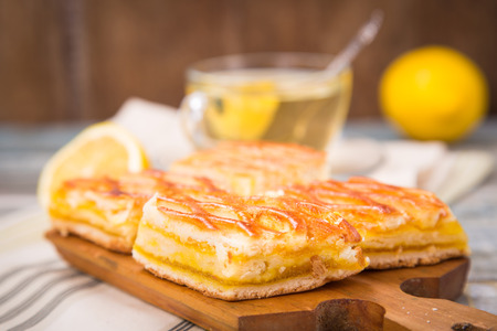 lemon pie: tarta de lim�n fresco con t�, frutos de lim�n en la placa de madera Foto de archivo